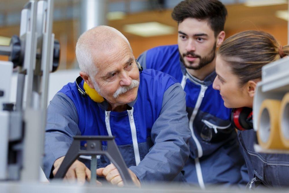 no mercado de trabalho, profissional mais experiente compartilha experiencia com colegas